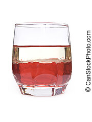 glass with red liquid and layer of oil on a white background