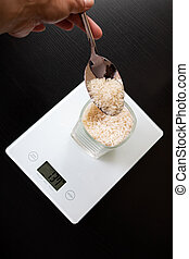 Glass with rice on electronic scales and spoon