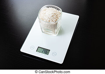 Glass with rice on electronic scales on wooden table