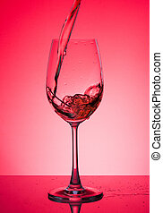 Glass with rose wine on a red background