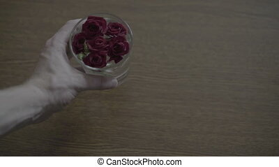 Glass with roses on the table