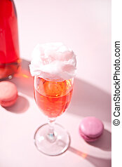 Glass with sweet cotton candy pink cocktail and bottle on background
