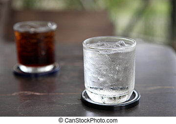 Glass with water and cola on wood background