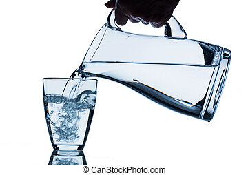 glass with water and jug - pure water is emptied into a...