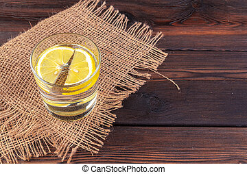 Glass with water and lemon on wooden table