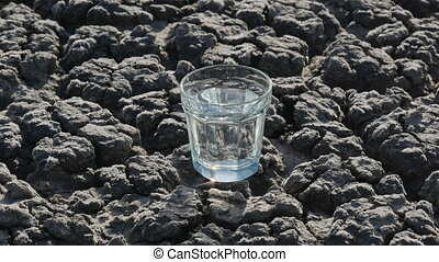 Glass with water at dry textured land - Glass with clear...