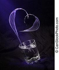 glass with water in the form of heart on a black background