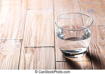 Glass with water on a brown wooden table
