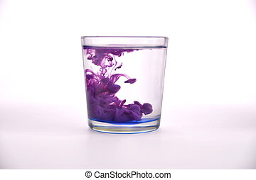 Glass with water on a white background with purple paint