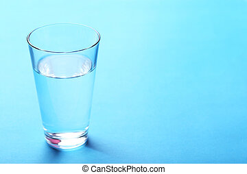 Glass with water on blue background