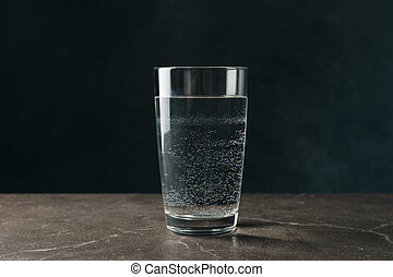 Glass with water on gray table, close up