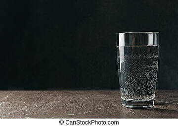 Glass with water on gray table, space for text