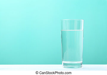 Glass with water on mint background