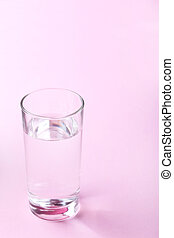 Glass with water on pink background