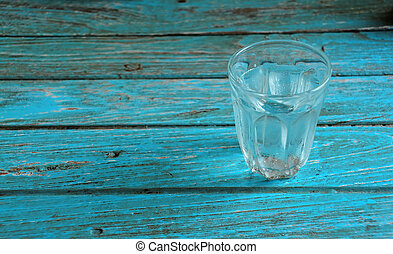 Glass with water on the cyan wood