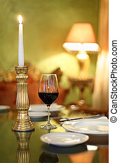 glass with wine and candlestick with candle at table in cozy restaurant; shallow depth of field