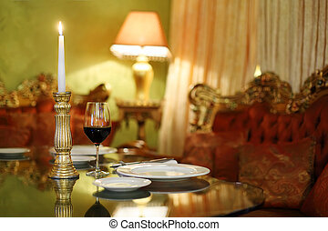glass with wine and candlestick with candle at table, red sofa in restaurant; shallow depth of field