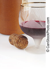 Glass with wine, cork and clay bottle