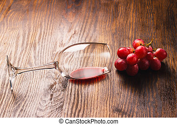 Glass with wine next to the bunch of grapes