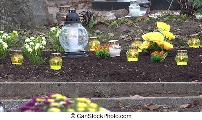 yellow candle burning on grave earth in cemetery.