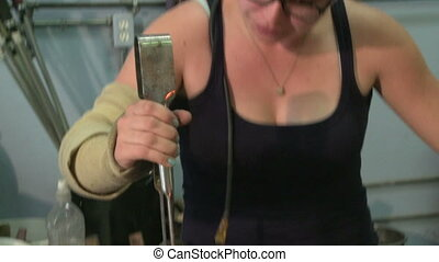 Glassblower tilt down 3 - Medium shot tilt down from...