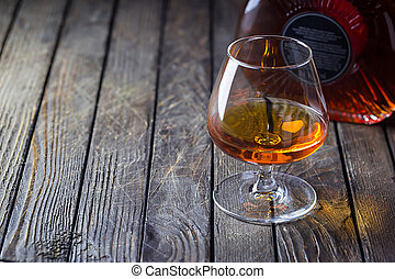 Glasse of brandy or cognac and bottle on dark background.