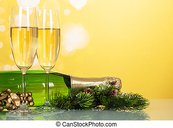Glasses and a bottle of champagne, pine branch with cones, on bright shimmering