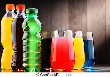 Glasses and bottles of assorted carbonated soft drinks in...
