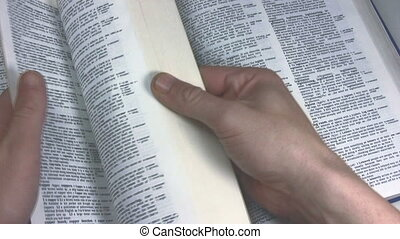 Hand, browsing through the pages of a dictionary, looking up the word copyright, placing a pair of glasses on the page