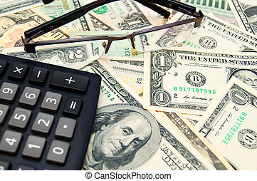Glasses and the calculator on banknotes (dollars).