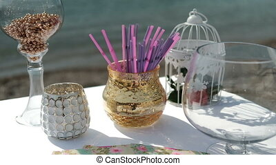 Glasses and vases on table by sand seashore. Transparent...