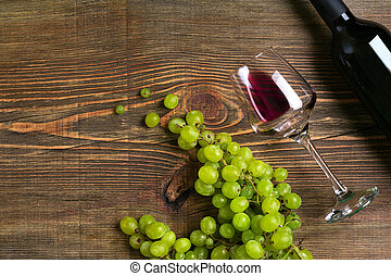 Glasses, bottle of red wine and grape on a wooden table. Top view. Copy space. Flat lay. Still life