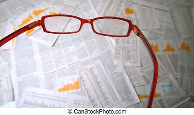 Glasses falling on papers with numbers and graphs in slow...