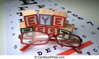 Glasses falling onto eye test with wooden blocks spelling...