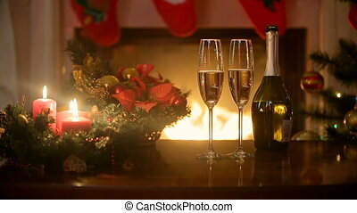 Glasses filled with champagne and burning Christmas candles on table at fireplace in living room