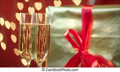 Glasses filled with champagne and gift box
