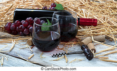 Glasses filled with red wine plus bottle and grapes in background on white rustic wooden boards