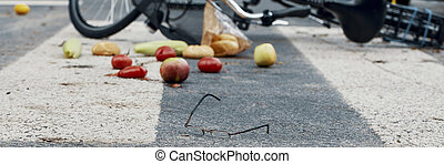 Glasses, groceries and a bicycle on an empty road crossing - panorama of a dangerous car accident concept