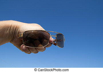 Glasses in hand man on a background of blue sky