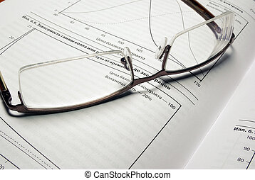Glasses laying on book with financial charts.