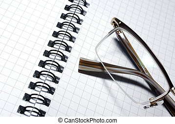 Glasses laying on spiral notebook. Business concept.