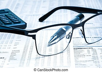 glasses near calculator with pen on financial newspaper