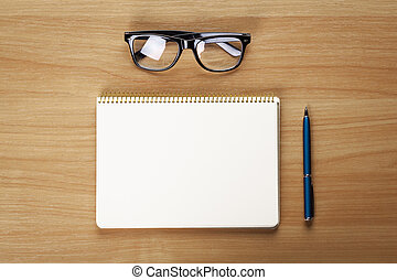 glasses, notepad with pen lying on the table