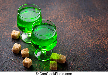 Glasses of absinthe with brown sugar - Glasses of green ...