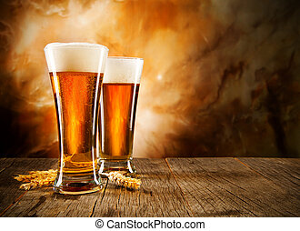 Glasses of beer on wooden table