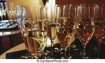 Glasses of champagne and white sparkling wine in golden ...