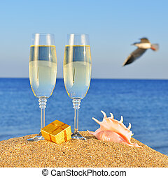 Glasses of champagne, box with a gift and seashell on the...