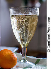 glasses of champagne on background with mandarin