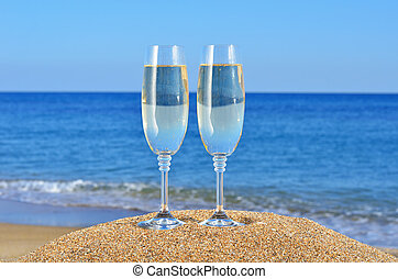 Glasses of champagne on the beachan