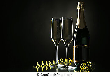 Glasses of champagne with bottle on a black background